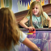 BRYAN EATON/Staff photo. Kally Jackman, 7, of Amesbury stops a shot by Niveah Currer, 7, of Salisbury in a game of air hockey at the Boys and Girls Club in Salisbury on Wednesday morning. The club is open today and tomorrow, but closed on Monday and New Year's Day.