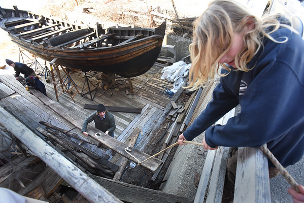 BRYAN EATON/Staff photo. Lokys Saffo, 14, of Merrimac lowers down the rotted planking taken from the bottom of the shallop.