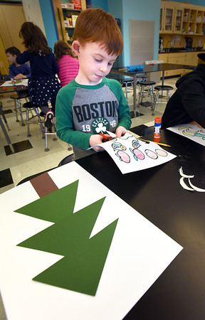 BRYAN EATON/Staff photo. Students in kindergarten art class were decorating evergreen trees with fruit for animals to eat on Monday afternoon. Jack Melander, 6, cuts around the fruit which he used colors of what the real fruit would be.