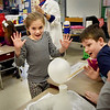 "BRYAN EATON/Staff photo. Avery Neale, 8, and Jacob Piskadlo, 7, react as a balloon expands though a chemical reaction of vinegar and baking soda at the Cashman School in Amesbury. Rita Advani, rear, of Hightouch Hightech brought the science program ""What's the Matter"" teaching students about the different states of matter that affect everyday life."