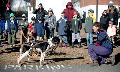 JIM VAIKNORAS/Staff photo Jessica Johnson and Undertaker demonstrate dog sled commands for Cub Scout Pack 7 of Salisbury and Pack 21 of Newburyport Saturday morning at the Star of the Sea Church in Salisbury. Jessica visited with her uncle Jeff McRobbie, a professional dog sledder from Maine.