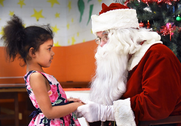 BRYAN EATON/Staff photo. Santa Claus made a stop to the Boys and Girls  Club in Salisbury on Wednesday afternoon to present an early gift to youngsters there who had a pizza party afterwards. Jadalynn Aponte, 6, of Salisbury listens to Santa as he asks her what she would like him to deliver late Christmas Eve.