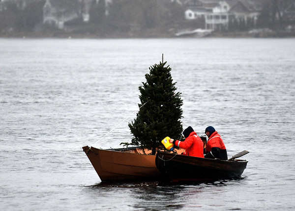 JIM VAIKNORAS/Staff photo Alice Twomblyand Aaron Cross bailout a dory with a Christmas Tree in the rain at Lowell's Boat Shop's open house Sunday afternoon in Amesbury.along with getting out of the rain, the event included games and crafts for kids, rum for the adults,music, food, a silent auction, and lots to see for everyone.