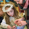 BRYAN EATON/Staff photo. Dressed as an angel Caroline Green, 5, gets help from her mother Lindsay as she creates a gingerbread house using stickies in Melissa Duguie's kindergarten class at the Bresnahan School in Newburyport on Tuesday. The were having Gingerbread House Day where parents helped celebrate the popular confection with various activities incorporating literacy, math and arts and crafts and enjoying refreshments.