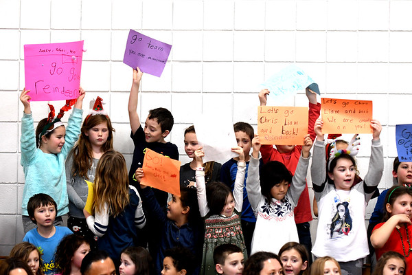 JIM VAIKNORAS/Staff photo Students hold signs and cheer on their classmates as they compete in the annual Reindeer Races at Salisbury Elementary School Friday afternoon. Teams of 3 took turns pushing and riding on gym mats on top of carts with wheel in the school gym.
