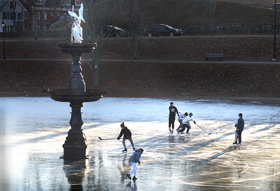 BRYAN EATON/Staff photo. Younsters play hockey on the ice at the Frog Pond at the Bartlet Mall on Tuesday afternoon. Skating there may be short-lived as rain is in the forecast for Saturday with the temperature in the mid-40's.