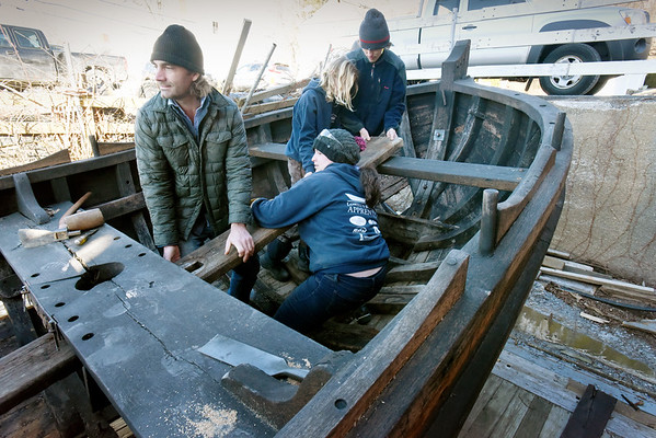 BRYAN EATON/Staff photo.  Graham McKay and his team of high school aprentices at Lowell's Boat Shop are restoring a replica of a shallop which was used on the Mayflower to bring crew and passengers to shore from the mother ship. Here they work to remove a board from the bottom of the boat which is rotted.