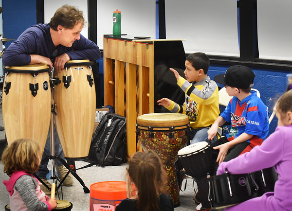 BRYAN EATON/Staff photo. Drum teacher Tomas Havrda, left, listens to Damien Pearson, 8, as he tries a certain beat at the Boys and Girls Club.