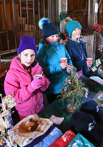 JIM VAIKNORAS/Staff photo Emily Balukas, 7, Samantha Morris,10, and Isla DeVivo, 11, take a hot chocolate break as they sell items at the North East Equine Rescue open house in west Newbury Saturday.