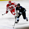 JIM VAIKNORAS/Staff photo Triton's Sam Rennick clears teh puck against Melrose's Cam Marks at Kasabuski Rink in Saugus.
