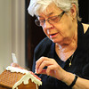 Newburyport: Ruth Whitney of Newburyport attaches mint candies to the roof of her gingerbread house. Bryan Eaton/Staff Photo