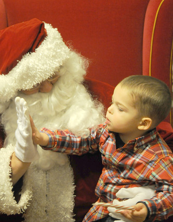Newburyport Jimmy Manning, 2, gives Santa a high five at the annual Sing-Along at the Emma Andrews Library in Newburyport wednesday nigh. Jim Vaiknoras/staff photo