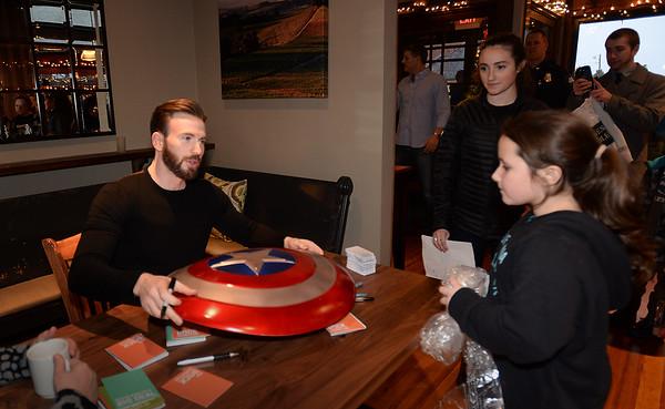BRYAN EATON/ Staff Photo. Shae Gallagher, 9, of Newburyport hands Chris Evans a Captain America shield to autograph.