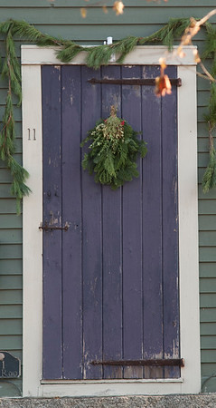 """Is the holly that will be, on your own front door.""<br /> JIM VAIKNORAS/Staff photo Garland and a wreath with holly decorate this door on High Road in Newbury."
