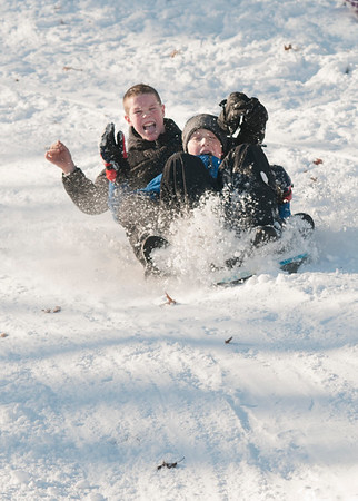 JIM VAIKNORAS/Staff photo Miles McGee, 12, and Tuna Sava, 13, kick up some snow as they make a sledding run on Marches Hill in Newburyport Sunday.