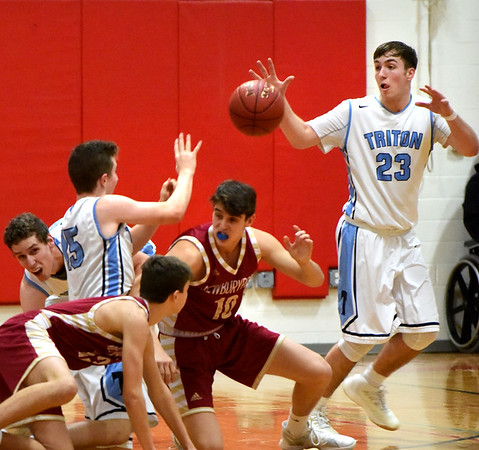 BRYAN EATON/Staff photo. Triton's Kyle Odoy passes to William Parsons after hitting the court with two Newburyport players.