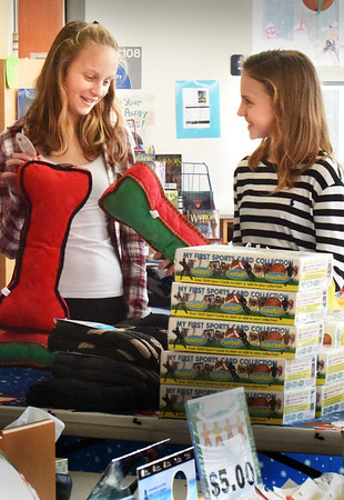 BRYAN EATON/Staff photo. Ava Mullen, left, and Ashley Jones, both 11, check out the items for sale at the Holiday Shop at Salisbury Elementary School on Monday. The event, sponsored by the school's PTA, is not a fundraiser, but affords students the chance to buy gifts for friends and family at affordable prices from goods obtained from local merchants.