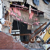 BRYAN EATON/Staff photo. The stairway leading to the third floor can be seen as debris falls.