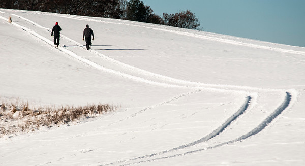 JIM VAIKNORAS/Staff photo Two people and a dog walk along a cross-country ski path at Woodsom Farm in Amesbury Sunday morning.