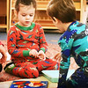 BRYAN EATON/Staff photo. Tess Barrett, left, and Nolan Salski, both 3, put colored pegs into holes of matching colors on pictures of fish at the Newburyport Montessori School while wearing their PJ's. The school held Pajama Day to coincide with a drive to collect pajamas for the Pettengill House in Salisbury.