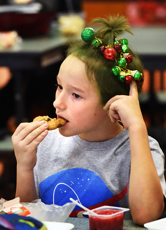 BRYAN EATON/Staff photo. Connor Forisso, 8, enjoys his lunch at the Cashman Elementary School in Amesbury with dyed green hair and Christmas ornaments in his hair. It was Crazy Hair Day at the school, part of Spirit Week leading up to school vacation.