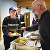 BRYAN EATON/Staff photo. Volunteer Henry Goodwin ladles on the gravy for veterans Norman Bellavance, and Gary Eichenlaub of American Legion Post 187. The were at the annual Support Our Troop Christmas dinner, sponsored by Amesbury Veterans of Foreign Wars Post 2016 at Holy Family Parish Hall on Wednesday night.