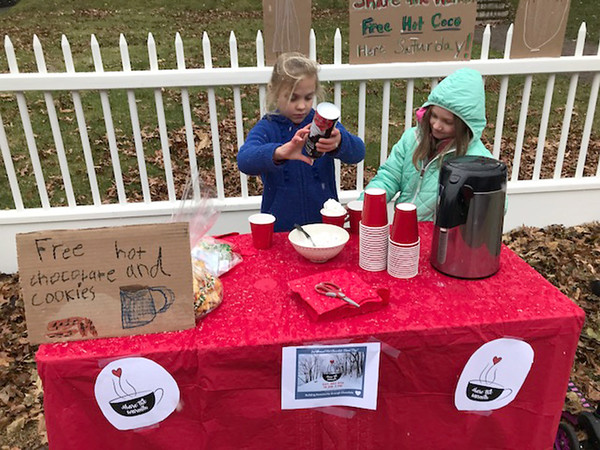 DAVE ROGERS/Staff photo Lorelei Horan, 7, left, and Beatrix Eigerman, 7, were busy serving hot chocolate Saturday morning on High Street as part of the citywide Share the Warmth event.