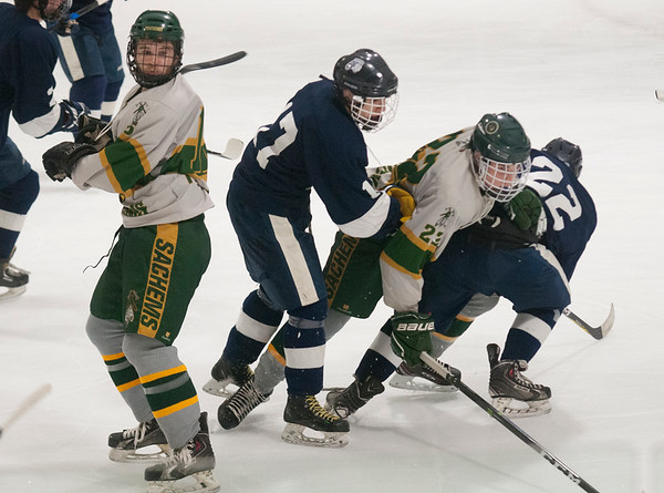 JIM VAIKNORAS/Staff photo Pentucket's #22 Jason Porter and #5 Josh Smith get tangled with  Lynnfield players during their game at Veteran's Rink in Haverhill Wednesday night.
