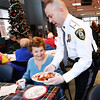 BRYAN EATON/Staff photo. Paolina Naples smiles as Amesbury Police Lt. Criag Bailey delivers glazed ham to her table followed by diffents kinds of quiche and fresh fruit. They were at the Amesbury Senior Center for Breakfast With Chiefs where there was a visit by Santa Claus in addition to gifts and the free meal.