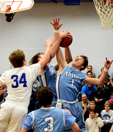 BRYAN EATON/Staff photo. Georgetown's Colin Dow, Triton's William Parsons and Gabriel Butts reach for the ball.