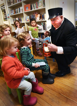 "BRYAN EATON/Staff photo. ""Conductor"" Donald Roberts clicks the tickets of children who appeared for the Emma L. Andrews Library's first Polar Express event on Thursday afternoon. He read them the story and then they got to drink hot cocoa and cookies at the Newburyport community center."