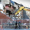 BRYAN EATON/Staff photo. Two bystanders watch as the demolition ends on Monday afternoon.