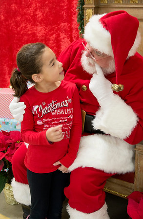 """"""" Jolly old Saint Nicholas lean your ear this way"""" <br /> JIM VAIKNORAS/Staff photo Adison Moore, 6, has a chat with Santa at teh annual Newbury Elementary School"""