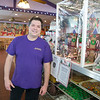 JIM VAIKNORAS/Staff photo Andy Arizzi of Andyman's Bakery in Amesbury poses next to a Gingerbread Castle being raffled off to benefit Lucy's Love Bus.