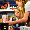 BRYAN EATON/Staff photo. Newburyport's Immaculate Conception School is holding Christmas shopping days for students to buy gifts for family and friends with older students helping the younger ones to choose gifts and help them with their math in deciding what to purchase with the money they've been allotted. Shopping with first-grader Sophia Davis, 7, left, on Monday is eighth-grader Campbell Pearce, 13.