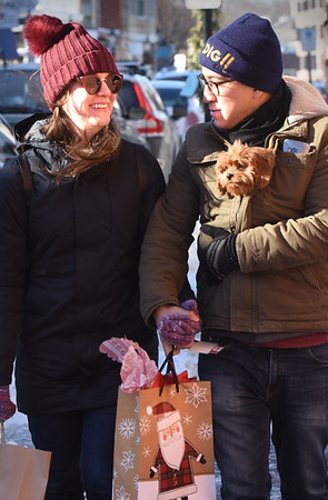 BRYAN EATON/Staff photo. Jenna O'Neil and Steven Cajamarca, with Lucy is his coat, are bundled up against the cold in downtown Newburyport. The two, from Amesbury, were doing some shopping in the downtown on Thursday afternoon.