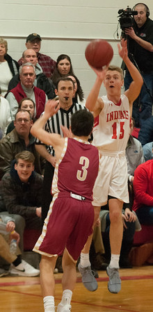 JIM VAIKNORAS/ Staff photo  Amesbury's Jaden Keliher shoots over Newburyport's Ryan Archie during the finals of the Mike Rowinski Tournament at Amesbury High School Thursday night.