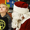 BRYAN EATON/Staff photo. Elijah Cameron, 7, of Salisbury thinks hard when Santa Claus asked him what he wants for Christmas, though he did get one after this photo was taken. They were at the Boys and Girls Club's Christmas party this week, where each child got a present and then got to eat some pizza and ice cream.