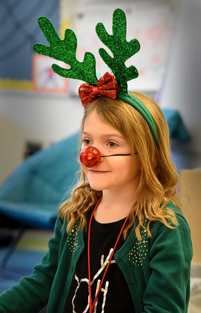 BRYAN EATON/Staff photo. Gemma Shakespeare, 8, wears antlers and a red-glowing nose like Rudolph the Red-Nosed-Reindeer in Arna Beaudoin's class at the Bresnahan School in Newburyport on Monday. They're celebrating Holiday Spirit Week with Monday as Merry Monday, and today is Snow Much Fun Tuesday and so on.
