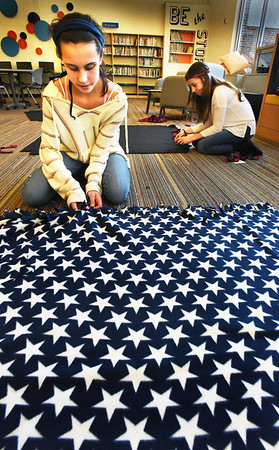 BRYAN EATON/Staff photo. Meghan Murray, left, and Fiona Dunphy, both 13, work on making blankets with other members of the Clipper Crew, an eighth grade leadership group at the Nock Middle School in Newburyport on Tuesday. They raised money to buy material and create the blankets for the Bedford VA Hospital.