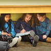 BRYAN EATON/Staff photo. Despite having a well-lit room complete with computers for doing homework, friends, from left, Tristan Vo, 9, Kayden Keating, 8, and Emma Lattime, 9, found space under a table in the boardgame room. They were at the Boys and Girls Club in Salisbury on Monday working on their cursive wrighting.