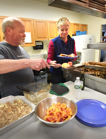 BRYAN EATON/Staff photo. Volunteer Richard Allen and Lisa Crocetti load a plate with breakfast casserole, sausage and fruit salas at St. Paul's Church in Newburyport yesterday morning. The church also put on a ham supper last night for those in need or in want of some fellowship.
