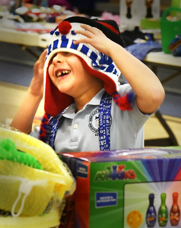 BRYAN EATON/Staff photo. Henry Gayton, 6, has fun checking out a hat while looking over items at the Immaculate Conception School's Christmas shopping day on Monday.