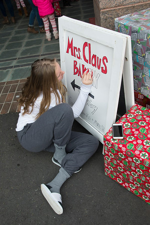 JIM VAIKNORAS/Staff photo Ella Bernard paints a sign for Mrs Claus Bakery at the Polar Express at the MBTA station in Newburyport Saturday morning. Over 3500 passengers rode the train sponsored by the Immaculate Conception in it's 17th year.