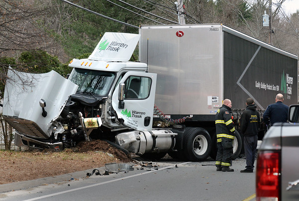 BRYAN EATON/Staff photo. The tractor trailer unit involved in the crash was heavily damaged but the driver escaped injuries.