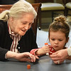 BRYAN EATON/Staff photo. Youngsters from the Newburyport Montessori School met with residents of Avita Assisted Living and Memory in Newburyport to created a mosaic over a peace sign of photos of children from around the world on Wednesday afternoon. Helping Tess Barrett, 3, of Newburyport glue the back of a photo was resident Jean Meurer. Afterwards the residents were treated to the children singing holiday songs with them.