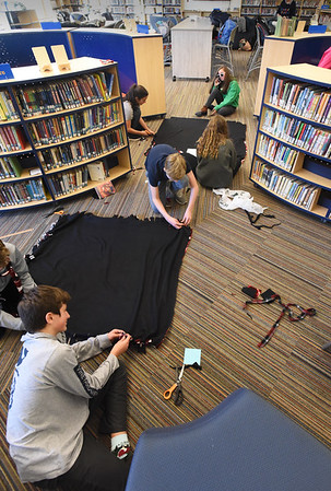 BRYAN EATON/Staff photo. The floor of the library at the Nock Middle School was covered in fleece as the Clipper Crew, an eighth grade leadership group made blankets for veterans at the Bedford VA Hospital.