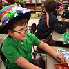 BRYAN EATON/Staff photo. Preston McAvoy, 7, made this hat with his mother which consists of colorful fabric, bows and ornaments and even lit up Christmas lights. It was Holiday Hat Day at the Cashman School in Amesbury on Monday, part of Spirit Week with a different theme each day.