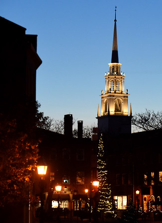 BRYAN EATON/Staff photo. The steeple of the Unitarian Church looms over the Christmas tree in Newburyport's Market Square as the temperature drops late Monday afternoon. There's a slight warming for today and tomorrow, though with rain in the forecast as well.