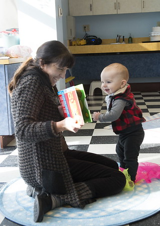 JIM VAIKNORAS/Staff photo Henry Mohler, 10 months, gets a close look as Anna McGrath reads a book to a group at Library Babies at the Newburyport Library Childrens Room Friday . The weekly class is a drop-in program for babies under 12 months and their caregivers.